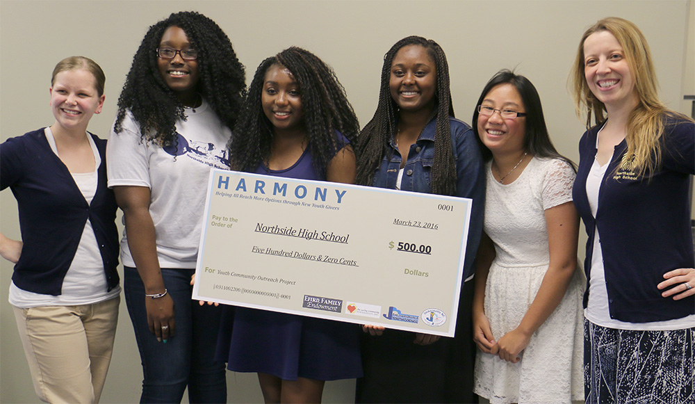 HARMONY giving giant check to group of women