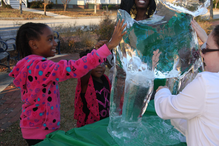 Young kids touching ice sculpture