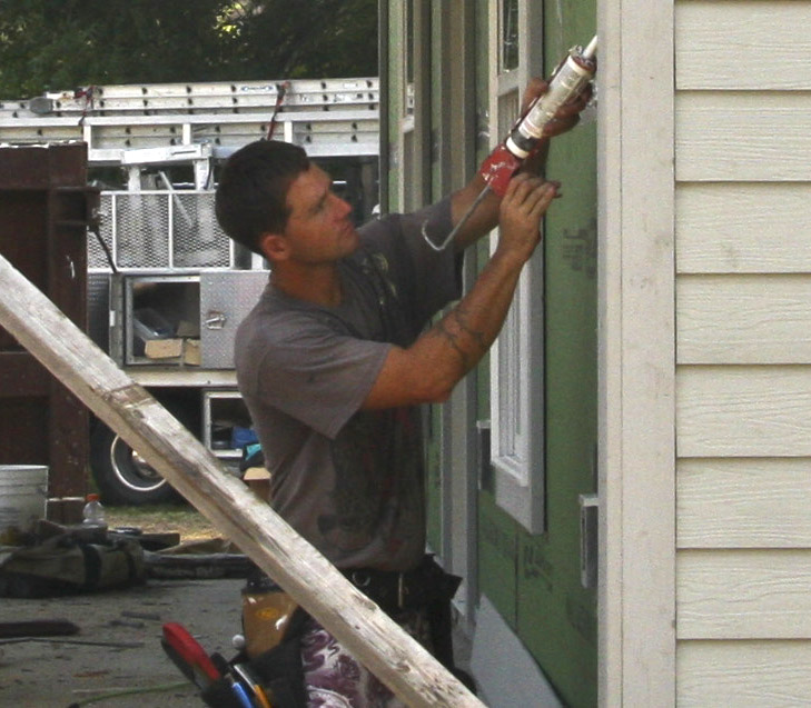 Man caulking a wall