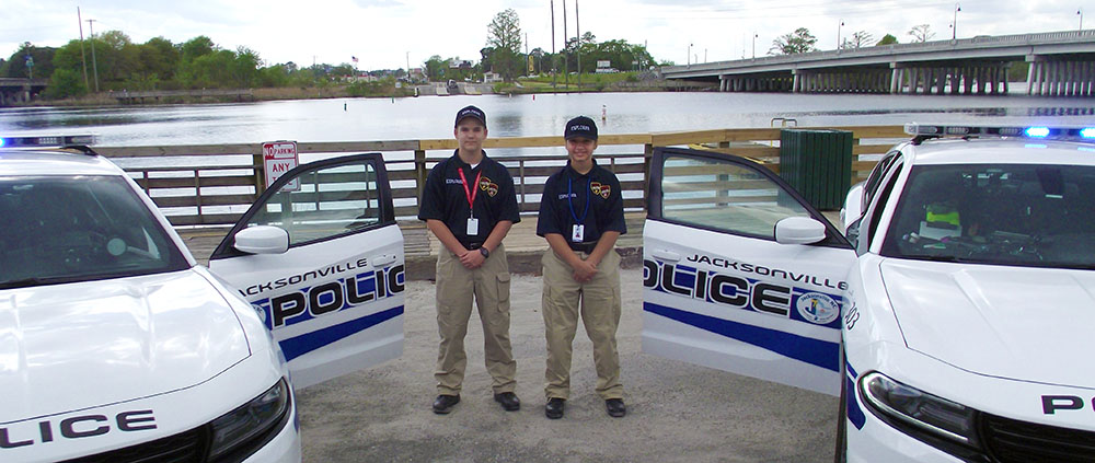 2 students in the Explorer Program with Police cars