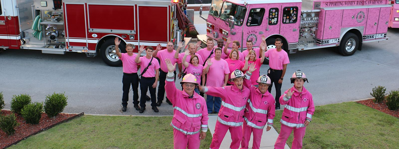 Firefighters and volunteers dressed in pink standing in front of a red firetruck and pink firetruck
