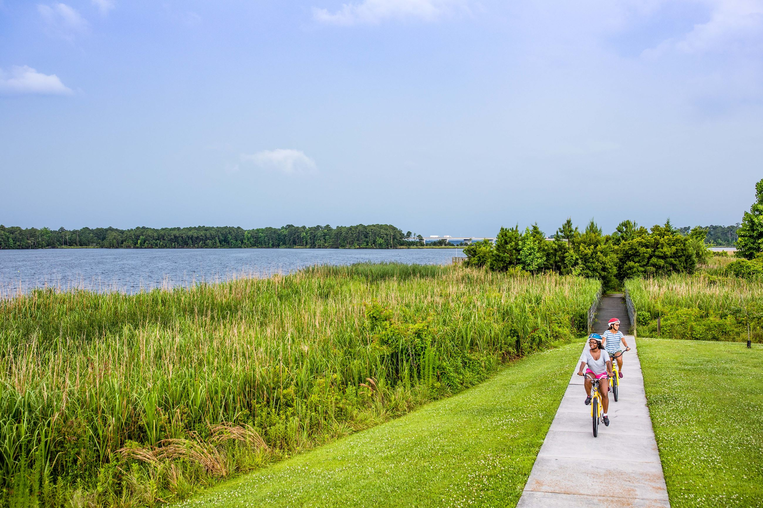 Jacksonville Shot of Two Girls Biking on Path Beside New River-websm